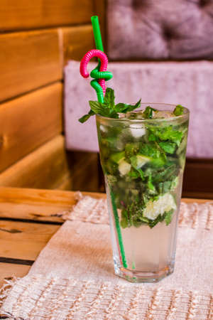 nonalcoholic: Photo of glass of drink non-alcoholic mojito with lime and mint with a straw on fabric napkin. Close-up photo Stock Photo
