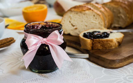 Jar of currant jam on table with loaf of bread, biscuits and orange. Healthy breakfast