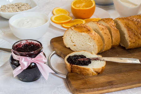 Jar of currant jam on table with loaf of bread, cream and oatmeal, orange. Healthy breakfast