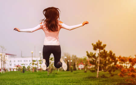air: Young girl jumping and having fun for spring and sun on green grass. Leisure and lifestyle