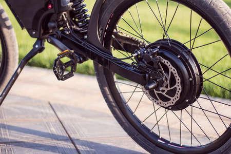 Elektrisches Fahrradmotorrad nah oben mit Pedal und hinterem Stoßdämpfer. Ebike-Fahrrad umweltfreundlicher Öko-E-Mountainbike-Transport. Gesunder Lebensstil Standard-Bild