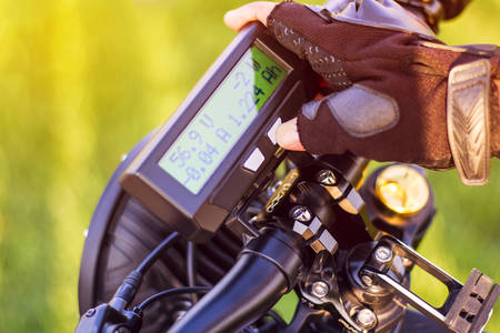 Close up of man hand clicking on mode button on monitor electric bike. Ebike bicycle environmentally friendly eco e-mountainbike transport. Healthy lifestyle Stock Photo