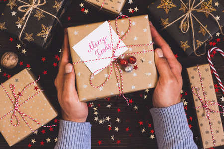 Man hands holding christmas holiday gift box with postcard merry xmas on decorated festive table with sparkle stars, candy cane, walnut on wooden background. Packaging gift wrap and ribbons, twine. Winter time new year
