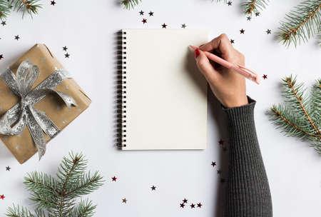 Gli obiettivi programmano i sogni fanno per fare la lista per la scrittura di concetto di natale del nuovo anno in taccuino. La penna di tenuta della mano della donna sul taccuino con l'abete si ramifica regalo su fondo bianco. Capodanno vacanze invernali Natale Archivio Fotografico