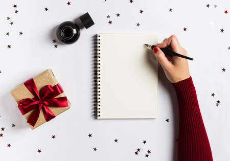 Goals plans dreams make to do list for new year christmas concept writing in notebook. Woman hand holding ink pen on notebook with gift red bow on white background. New year winter holiday xmas
