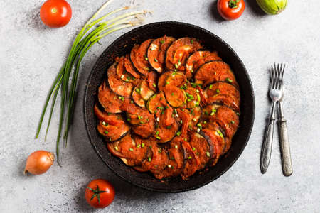 Ratatouille french provence dish of vegetables zucchini eggplant peppers and tomatoes in vintage frying pan on light background. Healthy tasty food