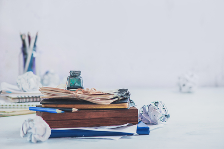 Header with writer workplace. Inkwell on a stack of drafts, pencil boxes and papers. High key still life. Creative writing concept with copy space. Archivio Fotografico