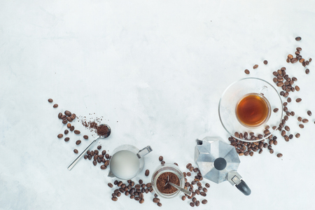 Header with brewing coffee ingredients. Moka pot, espresso cup, milk jug, ground coffee jar and coffee beans on a white concrete background with copy space. Creative food flat lay concept.