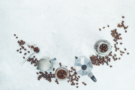 Creative food flat lay concept. Header with brewing coffee ingredients. Moka pot, espresso cup, milk jug, ground coffee jar and coffee beans on a white concrete background with copy space.