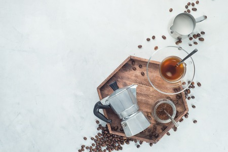 Wooden tray with Moka pot, espresso cup, ground coffee jar and coffee beans on a white concrete background with copy space. Header with brewing coffee ingredients.