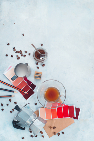 Color swatches of red and marsala in designer workplace. Moka coffee pot, color palettes, pencils, notes and coffee cups. Inspiration in alternative coffee brewing. Stock Photo