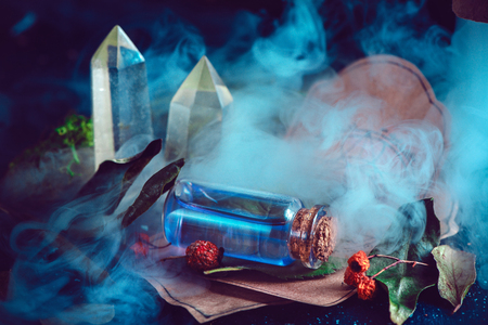 Magical still life with spells, herbs, potion ingredients and a glass bottle with mystic liquid on a dark background. Modern witchcraft concept with copy space.