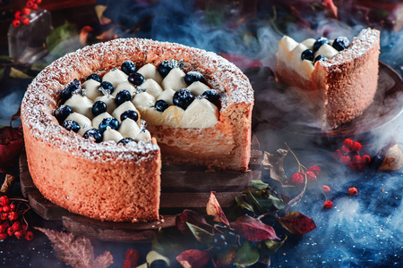 Cut cake with a shortbread crust on a dark background. A piece of cake with whipped cream and blueberries. Dark food photography with smoke. Traditional pumpkin pie in a Halloween still life with pastry. Contrast colors and soft focus.
