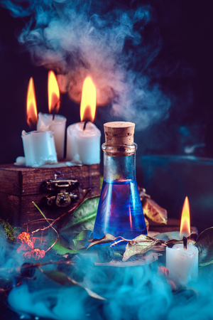 Magical still life with spells, herbs, potion ingredients, wax candles and a glass bottle with mystic liquid on a dark background. Modern witchcraft concept with copy space.