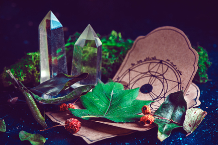 Pentagram drawing on a parchment with potion ingredients and crystals in a magical scene. Modern witchcraft concept with copy space. Dark still life photography.