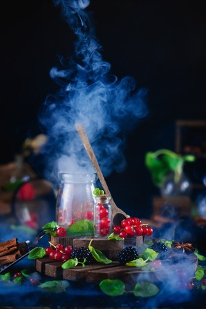 Jar with fresh berries, currant with wooden spoon and rising smoke on a black background. Laboratory and science concept. Magical still life with berry potion. Copy space.