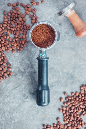 Coffee making equipment with copy space. Portafilter with ground coffee, tamper, cinnamon and beans on a marble background.