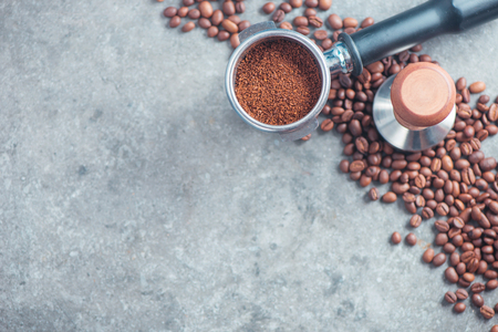 Equipment for brewing coffee flat lay. Portafilter with ground coffee, tamper, and beans on a concrete background with copy space.