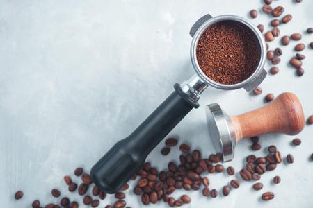 挽きコーヒークローズアップのポルタフィルター。コーヒーフラットを醸造するための機器は、コピースペースと明るい背景に横たわっています。