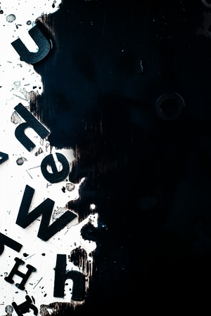 Scattered letters in blurring spilled ink. Creative writing concept. High contrast still life with creative writer workplace. Copy space. Banque d'images