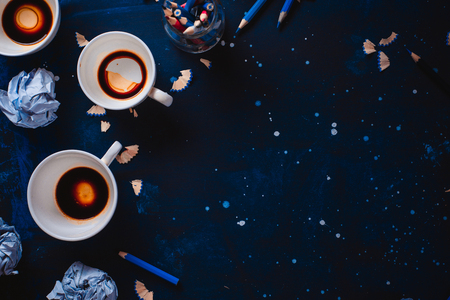 Dark background with crumpled paper balls, empty coffee cups, pencils, paper, notes and notepads. Still life with writer workplace. Creative writing concept.