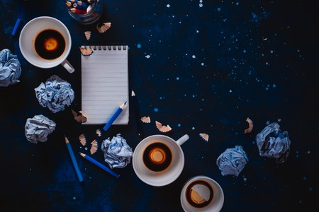 Creative writing concept with lined note paper, empty coffee cups, pencils and crumpled paper balls on a dark background. Editing and copywriting workplace.