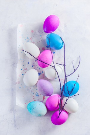 Easter eggs in a high key scene with a tree branch. A minimalist concept from above. Shades of blue, pink and purple. Stock fotó