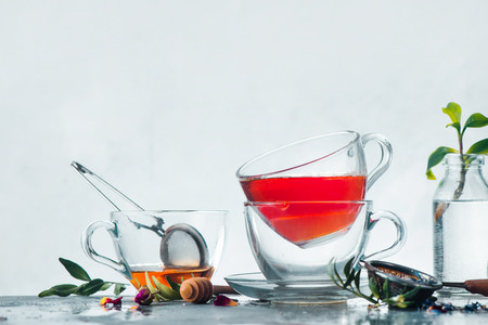 Stack of glass cups of tea on a white background with a honey spoon, tea strainer, fresh green leaves, flowers and copy space. Brewing herbal tea concept. High-key spring still life with copy space.