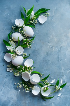 Half circle Easter vignette with white eggs, decorative green leaves and spring gypsophila flowers. Botany and floral decoration concept.