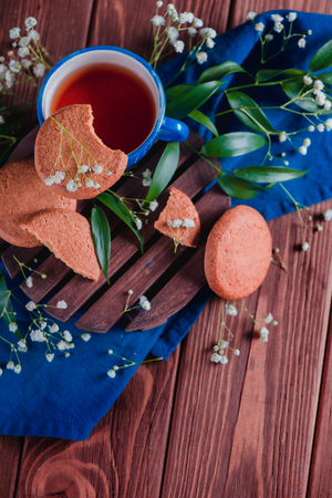 Cup of tea with oatmeal cookies and spring gypsophila flowers on a warm wooden background. Blue ceramic cup on a blue linen napkin. Breakfast scene with copy space.