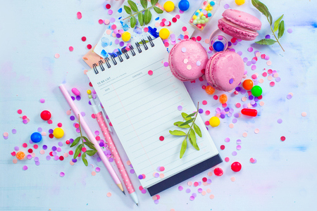 Open notepad with blank pages in an organizing a party concept with confetti, pink macarons, candies and sprinkles. Creative Event To-do list flat lay with copy space. Stock Photo