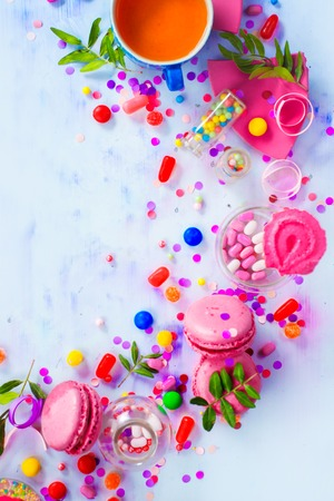 Pink macarons, candies, confetti and sprinkles in a creative party vignette with copy space. Colorful celebration flat lay.