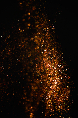 Golden glitter texture with a dark background. Defocused bokeh effect for a Christmas or wedding card.