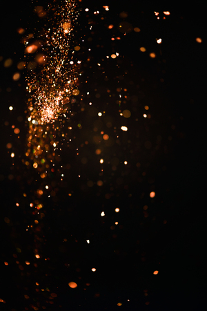 Glitter lights abstract texture. Gold defocused bokeh on a dark background. Card for Birthday, anniversary, wedding, New Year Eve or Christmas. Stock Photo
