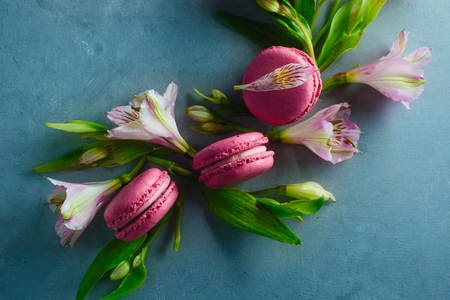 Pink macaroons decorated with pink and white alstroemeria flowers. Romantic French dessert on stone background with copy space. Stock Photo