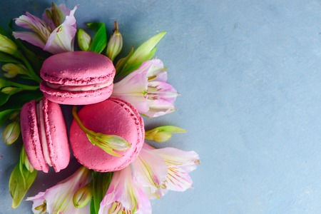 Macaroon cookies flat lay with spring blossom on a blue stone background with copy space. French desert close-up.