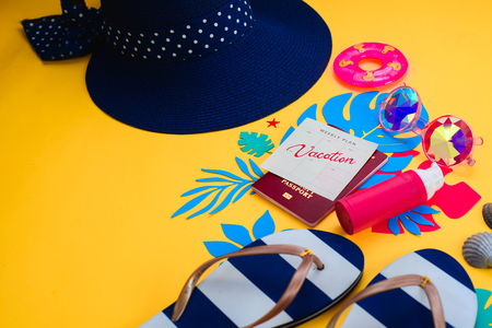 Traveling essentials from above. Vacation concept with tropical leaves, beach sandals, kaleidoscope sunglasses, tiny swim ring, broad-brimmed hat, sunscreen, seashells on a vibrant yellow background.