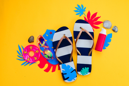 Accessoires voor zomervakanties, zonnebrillen, slippers, zonnebrandcrème, kleine zwemring, schelpen op een levendige gele achtergrond. Reizende benodigdheden plat liggen met kopie ruimte. Vrouwelijk blauw en roze palet.