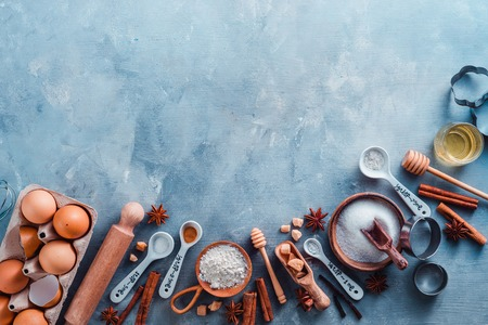 Cooking tools and ingredients concept flat lay with copy space. Baking header with measuring spoons, wooden scoops, whisks, rolling pin, cookie cutters, sugar, flour, eggs and cinnamon on a blue concrete background.