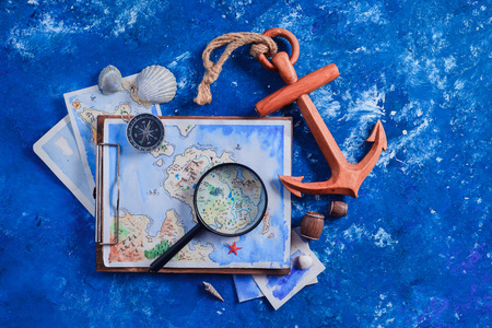 Travel flat lay with wooden anchor, fantasy map, watercolor sketches, seashells and compass on a navy blue background with copy space. Creative artist workplace in shades of blue Stock Photo