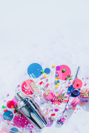 Shaker, straws and cocktail glasses flat lay on a white background with confetti, candies and sweets. Party drink concept with copy space.