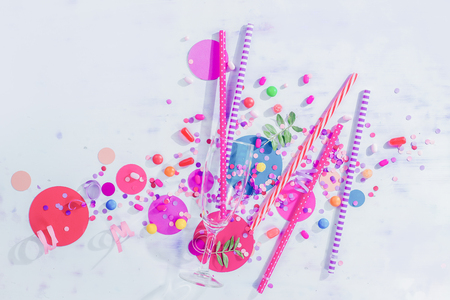 Champagne flute glass from above with straws, candies and confetti. Party concept with bar supplies, colorful flat lay with copy space