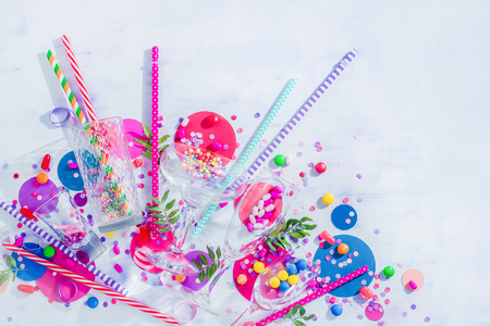 Cocktail glasses variety from above with straws, candies and confetti. Party concept with bar supplies, colorful flat lay with copy space