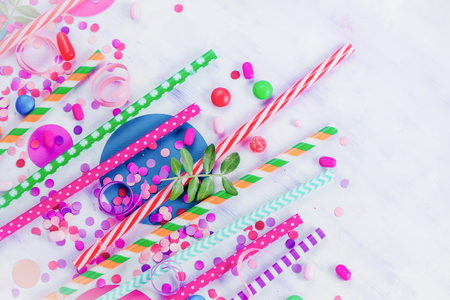 Colorful cocktail straws header with confetti and hard candies. Birthday or party greeting card flat lay with copy space.