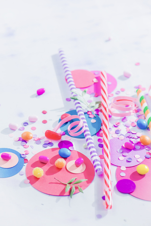 Cocktail straws, confetti and candies close-up in a colorful party supplies concept on a light background with copy space. Holiday accessories
