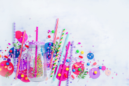 Milkshake straws, glass jar, confetti and candies close-up in a colorful party supplies concept on a light background with copy space. Holiday accessories