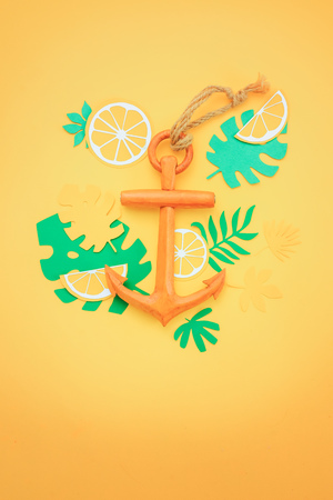 Wooden anchor on a bright yellow background. Summer vacation or travel flat lay with copy space