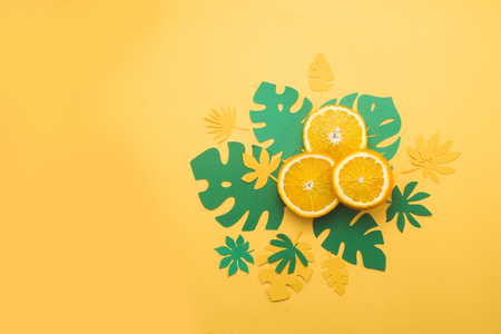 Fresh oranges with tropical leaves on a bright yellow background with copy space. Summer vacation flat lay with paper cutouts.