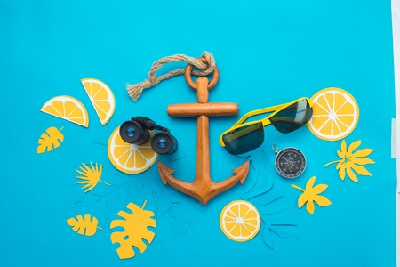Sea travel background with sunglasses, binoculars, anchor, compass and tropical leaves on a bright blue background. Summer vacation concept with copy space