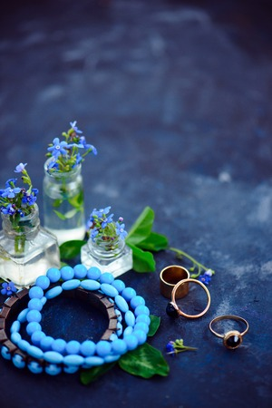 Blue bead bracelets and golden rings in a feminine style concept with blue flowers in tiny bottles on a dark background. Beautiful summer accessories with copy space